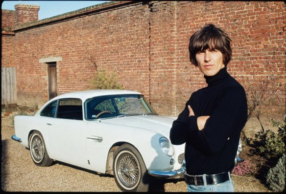 George Harrison next to his Aston Martin at his home in Esher, 1965. (Henry Grossman)