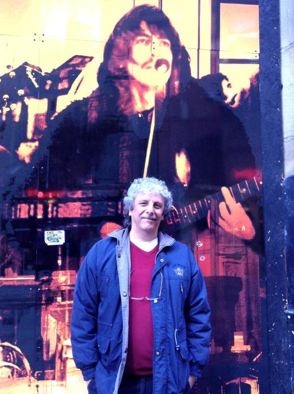 """Beto Iannicelli pousa com George Harrison ao fundo fazendo o acorde  um F#m7.  Harrison estava tocando a canção dos Beatles, """"Don't Let Me Down""""."""