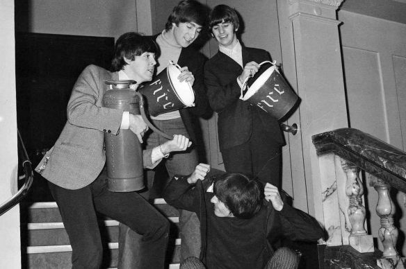 The Beatles cooling down at Liverpool Empire, November 1964. Standing left to right: Paul McCartney with a fire extinguisher, John Lennon and George Harrison holding buckets of water. Seated is George Harrison