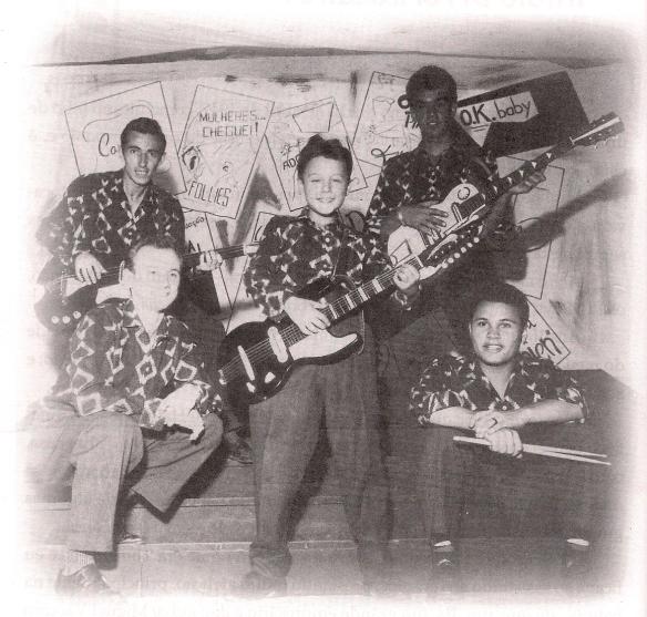 """Nenê no centro posando de guitarrista dos Rebels, e a indicação dos nomes dos colegas na foto, conforme suas próprias palavras: """"Embaixo da esquerda para direita ao meu lado, estão meu irmão Romeu e Prini Lorez. Acima José Carlos e Gaspar""""."""